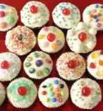 kids muffins - Chcolate fudge cake muffins, coated with with butter icing, and decorated with sprinkles, coloured sugar and sweeties.