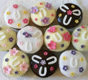 horseshoes - A selection of sponge and chocolate muffins decorated with a variety of different toppings with horseshoes and coloured flowers.