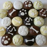Doggy Cakes - A selection of sponge and chocolate muffins decorated with a variety of different toppings and doggy decorations.