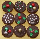 Xmas muffins - Our best selling chocolate fudge cake made as muffin cakes, topped with rich dark chocolate ganache and decorated for Christmas.