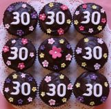 choc  '30' muffins - Our best selling chocolate fudge cake made as muffins and topped with a sophisticated ganache, which isn't over sweet.  Decorated with hand made sugar flowers for a 30th birthday.