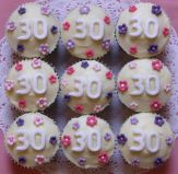 white '30' muffins - Our best selling chocolate fudge cake made as muffins and topped with a white chocolate and cream cheese icing, which isn't over sweet.  Decorated with hand made sugar flowers for a 30th birthday.