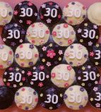 mixed '30' muffins - Our best selling chocolate fudge cake made as muffins and topped with sophisticated dark ganache or a white chocolate and cream cheese icing, neither of which are over sweet.  Decorated with hand made sugar flowers for a 30th birthday.