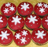 Snowflake Cakes - Sponge cake muffins decorated with red butter icing and hand cut snowflakes.