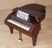 Grand Piano Cake - Our best selling cake, which we make in all shapes and sizes.  A moist chocolate cake with a melt in the mouth chocolate ganache topping.  A sophisticated cake, because it is not over sweet.  This time made in an unconventional shape as a grand piano.