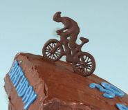 Cyclist Cake - Our best selling cake, which we make in all shapes and sizes.  A moist chocolate cake with a melt in the mouth chocolate ganache topping.  A sophisticated cake, because it is not over sweet.  This time made in an unconventional shape for a mountain biker's birthday.