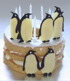 Penguin Cake - Layers of moist almond cake (gluten free) sandwiched together with lashings of whipped cream and lemon sauce, coated with lemon glace icing and decorated with hand made chocolate penguins.