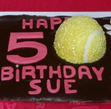 Tennis Ball Cake - Our best selling cake, which we make in all shapes and sizes.  A moist chocolate cake with a melt in the mouth chocolate ganache topping.  A sophisticated cake, because it is not over sweet.  Here decorated with lettering, paw prints and a hand made edible tennis ball.
