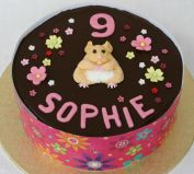 Hamster Cake - Our best selling cake, which we make in all shapes and sizes.  A moist chocolate cake with a melt in the mouth chocolate ganache topping.  A sophisticated cake, because it is not over sweet. With hand-made icing hamster and flowers.