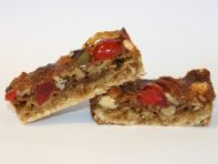 nutty shortbread slice - A rich butter shortbread base encrusted with a topping of mixed nuts and a scattering of glace cherries, all sealed in a gooey glaze.