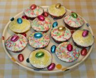 Easter Sponge Cakes - Sponge Cakes topped with glace icing and decorated with foil coated chocolate eggs, coloured sprinkles and coloured sugar.