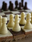 Chocolate Chess Set - Bought chocolate chess pieces placed on a board made from Millionnaire's shortbread cut into alternating squares of white and milk chocolate.  Variation could be made using white and milk chocolate buttons for a game of draughts.