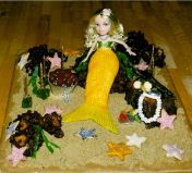 Mermaid Cake - Mermaid cake made using a plastic doll converted into a mermaid with icing, rocky road, star biscuits and sweeties.