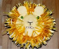 Lion Cake - Cake made in the shape of a lion's face with paper frill mane. The jaw was made to be mobile so the lion could roar, but this may frighten very small children!