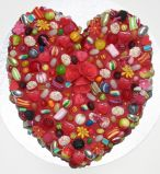 Sweetie Heart - A funky heart shaped cake coated with sweeties and hand made sugar flowers.